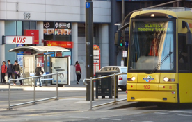 A long range shot of two pedestrian barriers along side the ramp to a tram stop, with a tram visible on the right.