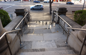 Looking down from some outdoor stairs, with stainless steel tube railing running down both sides.