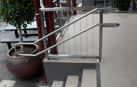 A double stainless steel tube handrail mounted near some outdoor steps.